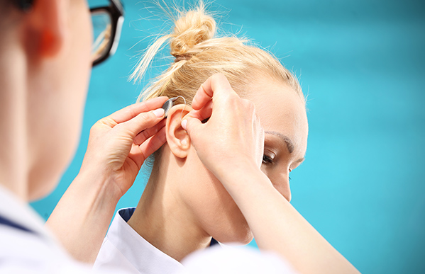 Audiologist fitting a hearing aid