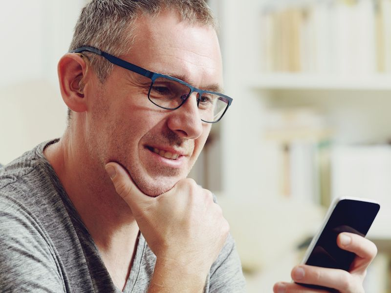 Man adjusting to new hearing aids by adjusting volume on his smartphone.