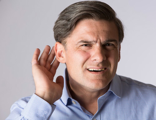 A man with his hand next to his ear trying to hear