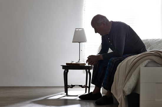 Elderly man sitting on bed alone