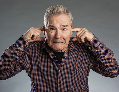 Man Holding his Ears | People Who Deny Hearing Loss