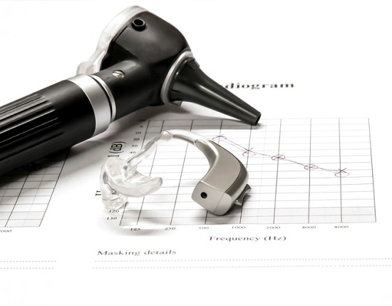 Otoscope and hearing aid on audiogram printout