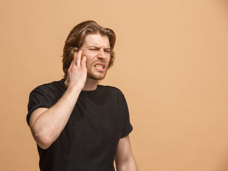 Man holding his ear because he has an ear infection that is causing hearing loss.