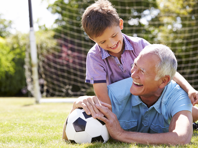 A man with hearing aids playing soccer with his grandson in a youthful way.