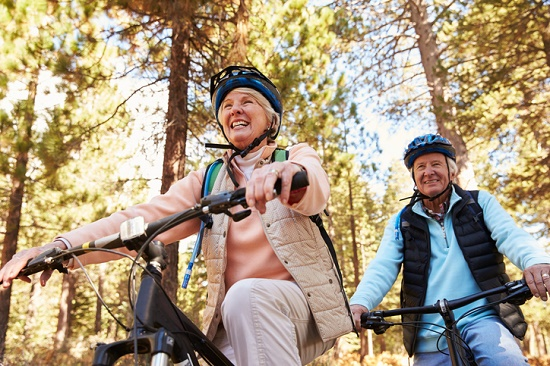 Older couple biking in the woods