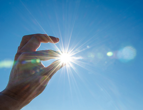 Picture of sun through fingers | 5 Secrets to Extending the Life of Your Hearing Aids