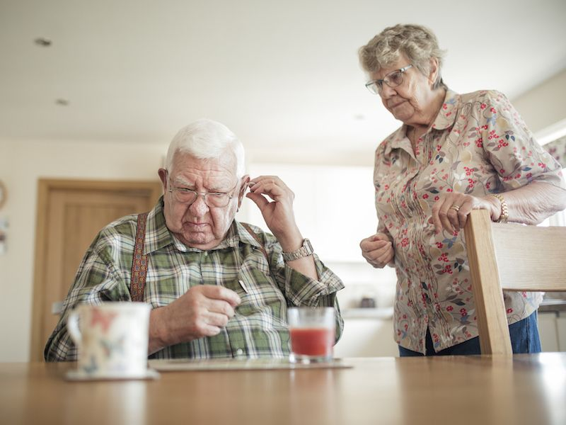 Man and his wife using tips to fix his hearing aids.