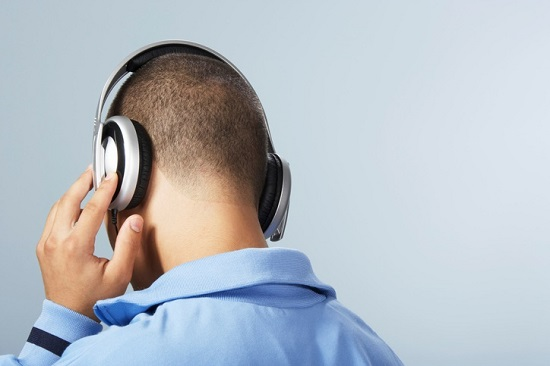 Teenage boy listening to music through headphones