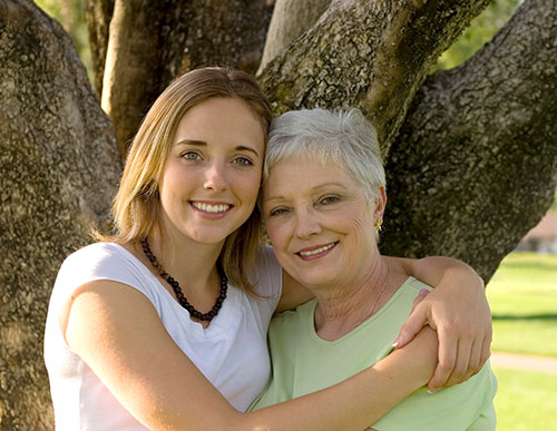 Happy Mother and Daughter under a Tree - 15 Ways Getting Hearing Aids Can Make You Richer and Happier