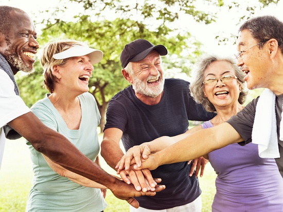 Group of older people smiling in a huddle with active gear