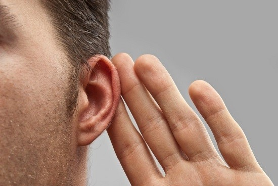 Man holding hand to ear simulating difficulty hearing