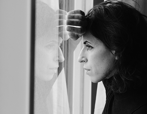 Black and white picture of sad woman looking out the window because of hearing loss.