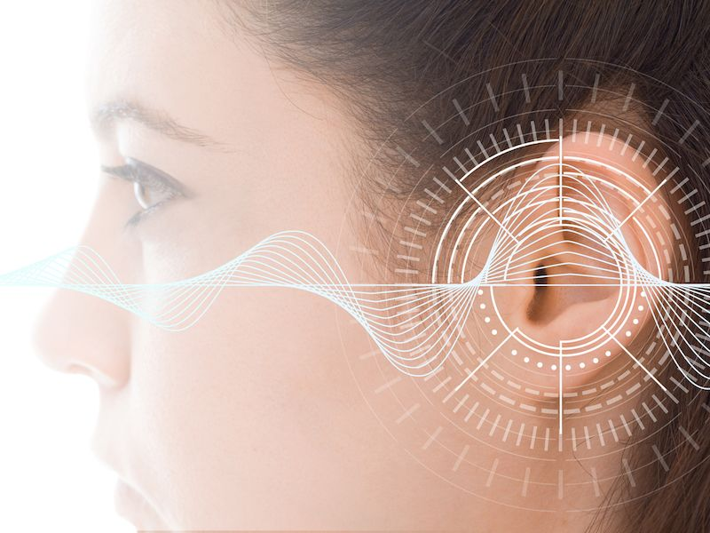 Image of woman getting hearing test with the results superimposed.