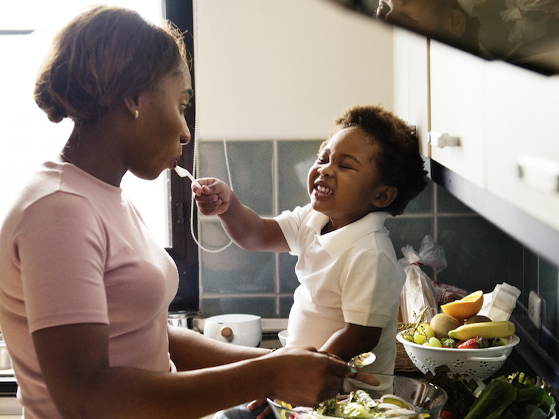 Grandma and grandson are cooking healthy food together in the kitchen to prevent hearing loss.