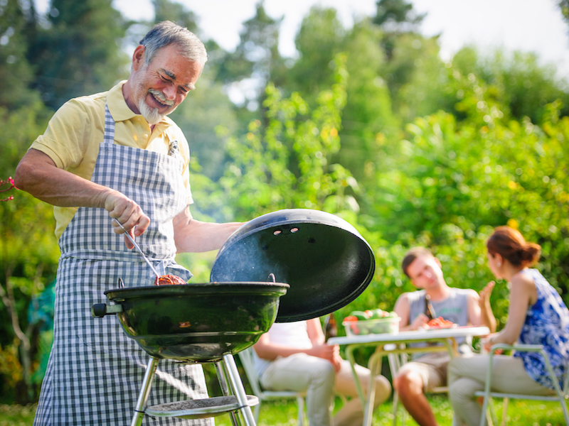 Man grilling unaware of his hearing loss and how getting a hearing aid could help him enjoy time with his family.