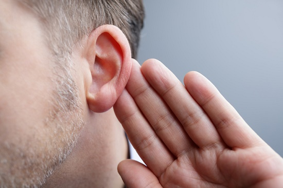 Man holding hand to ear struggling to hear