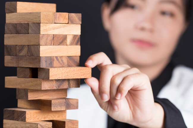 Woman pulling a Jenga block out as a metaphor for how ignoring mild hearing loss can become a larger issue.