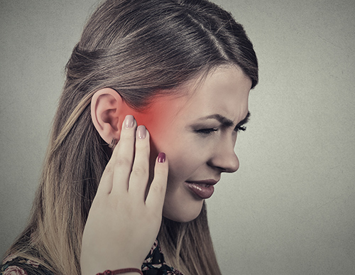 Woman holding her ear in pain from tinnitus