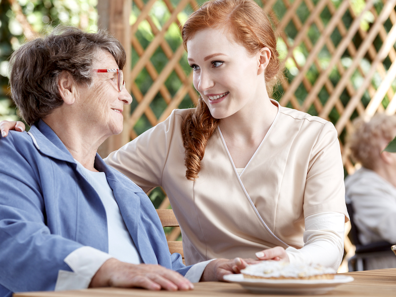 A young woman leans into an older woman to have a delicate conversation about hearing loss and hearing aids.