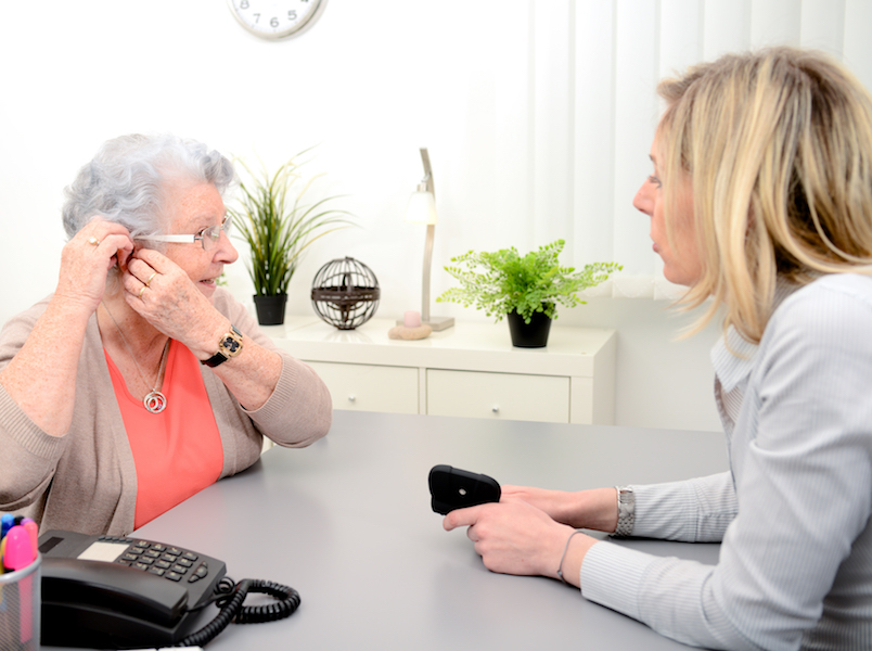 Woman is being fitted for her first hearing aid by an audiologist