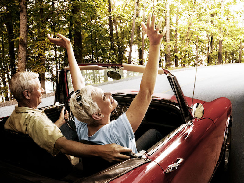 Woman with hearing loss happy to have her freedom and independence while riding in a convertible.