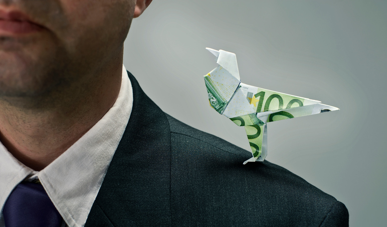 Man with mild hearing loss dressed for work with little bird made of money whispering in his ear.