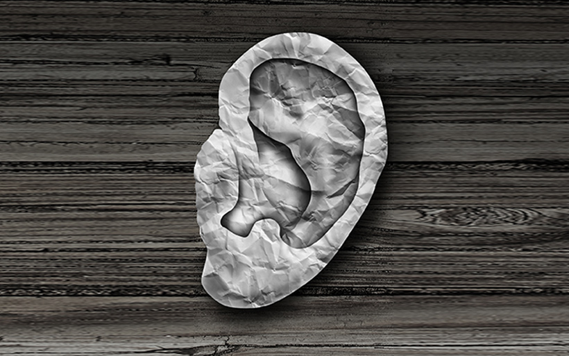 Picture of an ear made of paper on a wooden background.