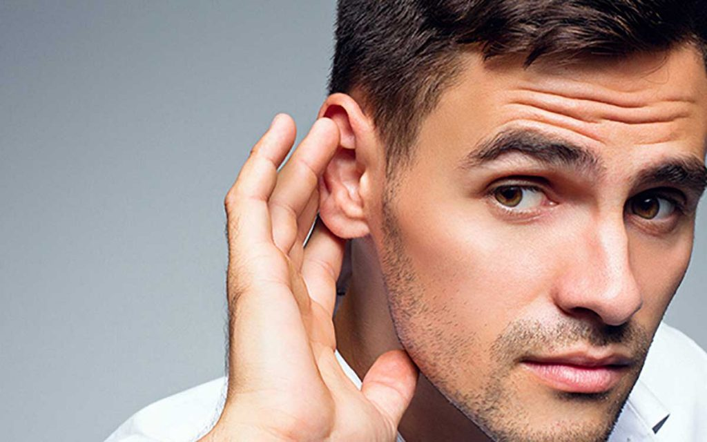 Man with his hand up to his ear
