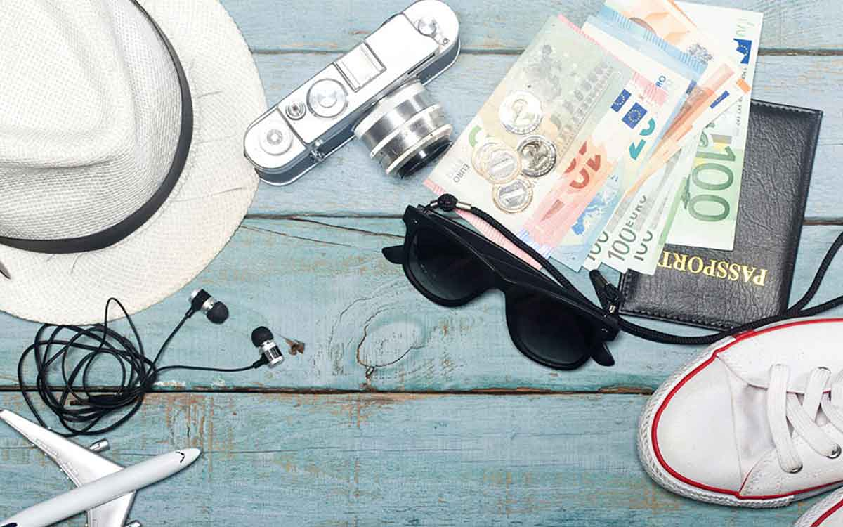 Picture of hat, glasses and money showing traveling items.