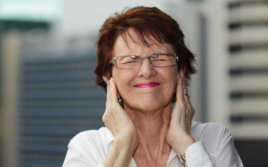 Woman with hands over her ears suffering from hearing aid feedback.