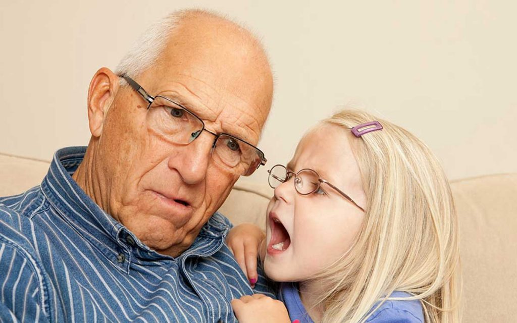 Elderly man suffering from single sided deafness leaning in to hear his grandaughter