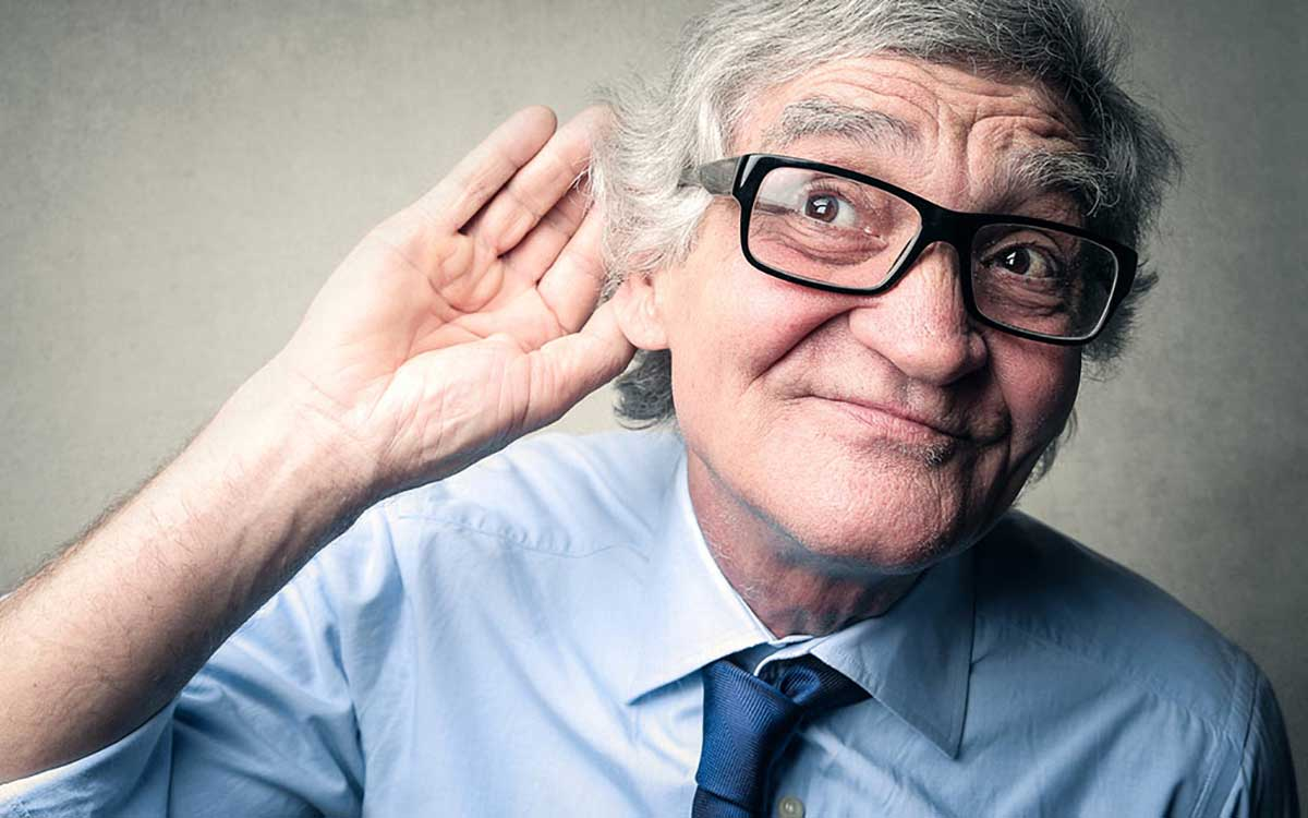 Man with his hand to his ear because of single sided deafness.