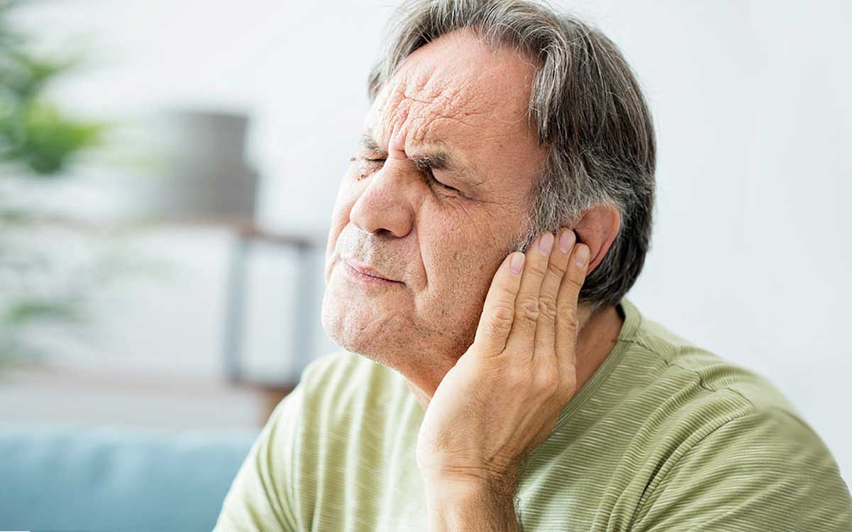 Man holding his ear because of Tinnitus