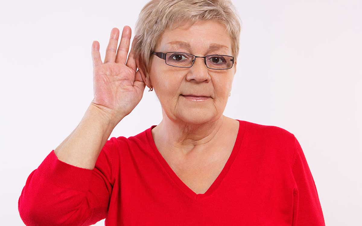 Woman with hand to ear because of hearing loss.
