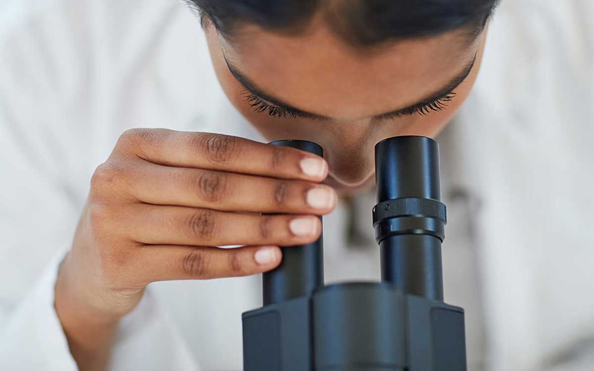 Scientist looking through microscope looking for hearing loss treatments.