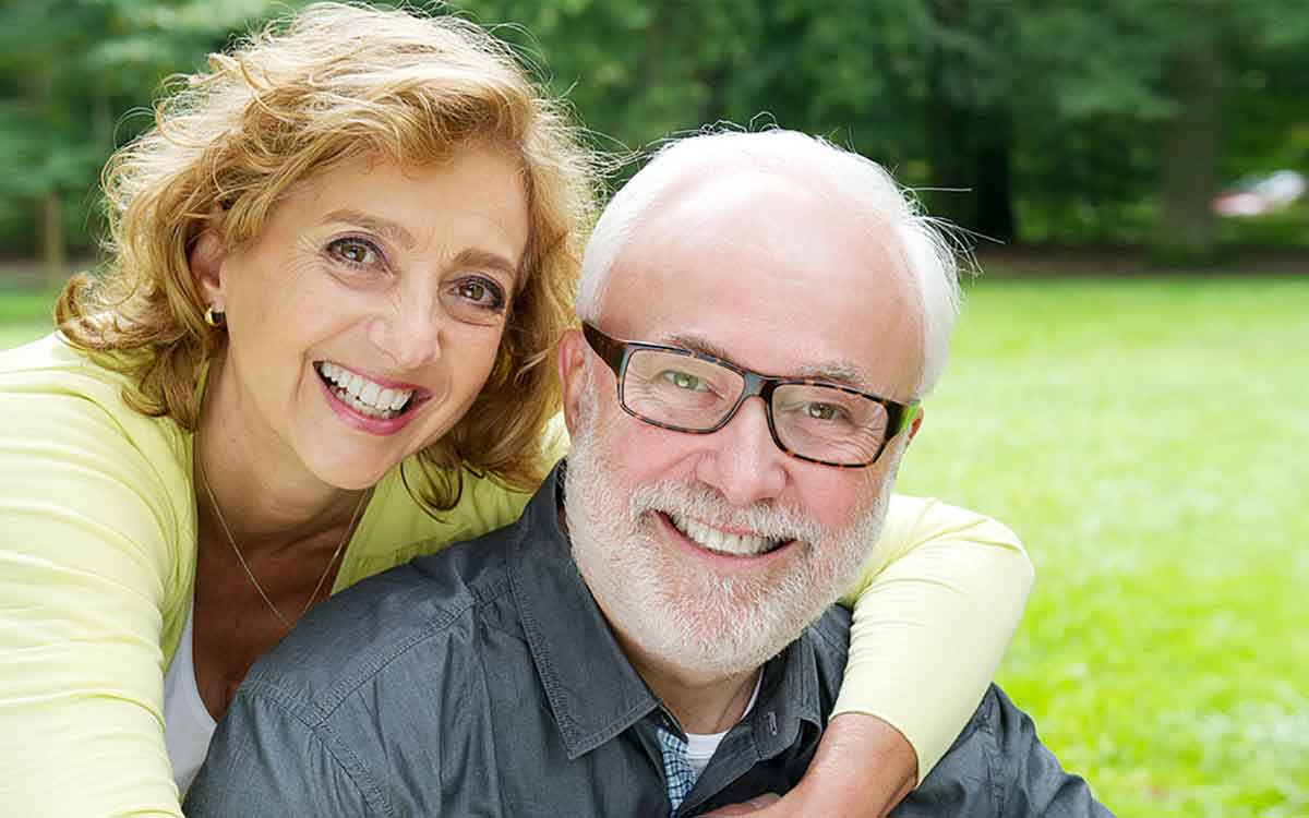 Happy middle aged couple wearing hearing aids.