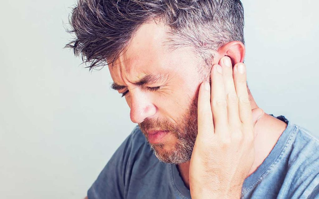 Man holding his ear because of Tinnitus ear pain.