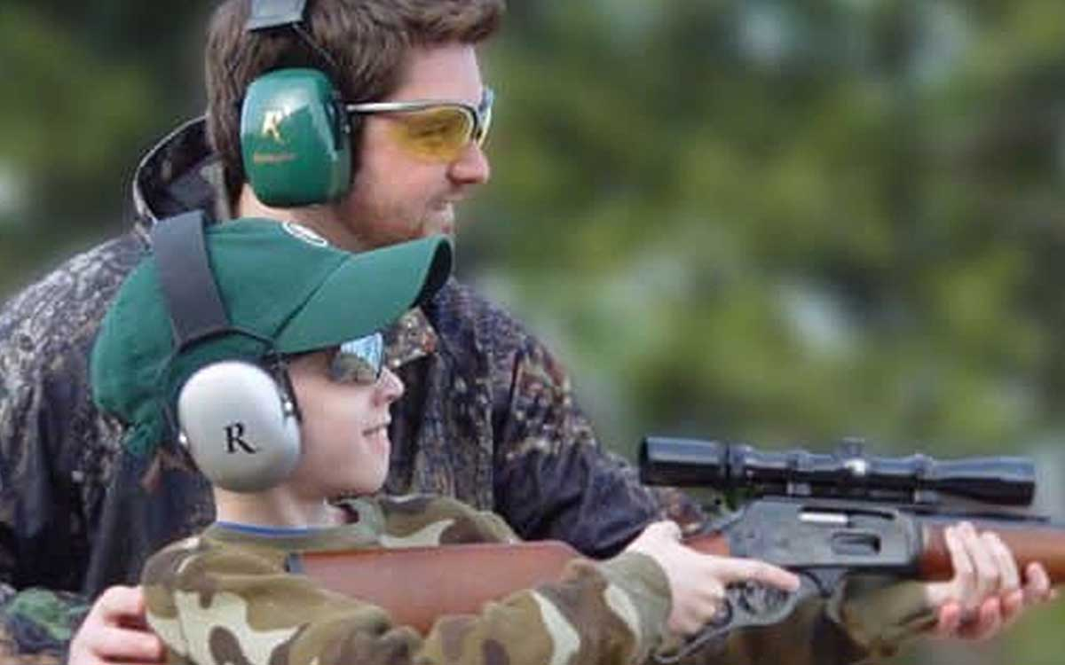 Father and son using ear protection to hunt.