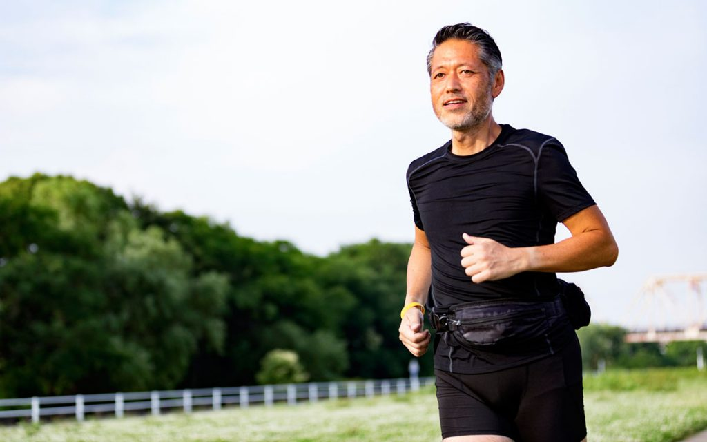 Man running with a fitness tracking hearing aid.