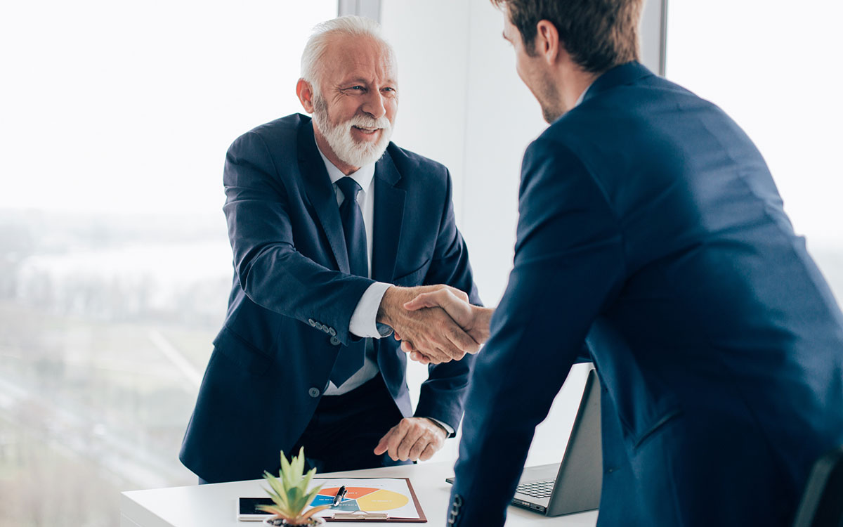 Business men shaking hands and successful because of hearing aids.