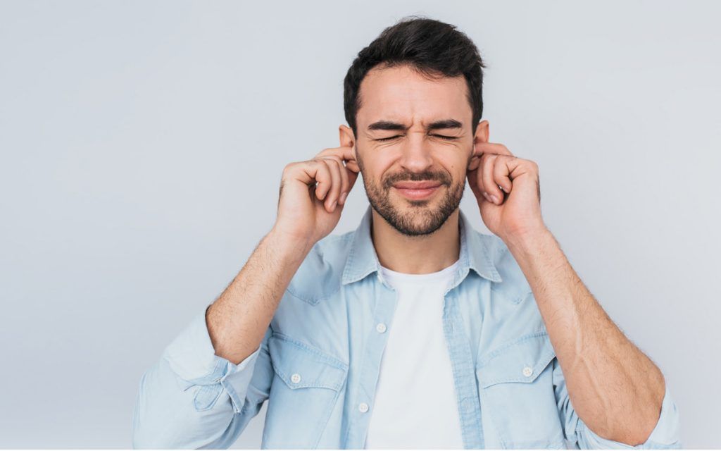 Man with hands over ears suffering from ear wax.