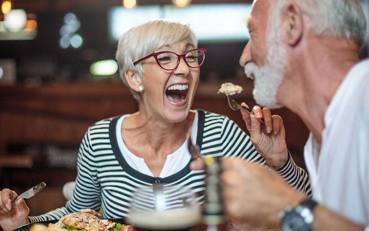 Two retired people having a conversation in a restaurant.