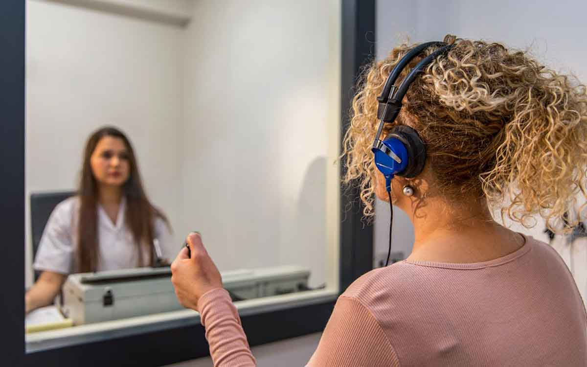 Woman in a booth getting a hearing test.