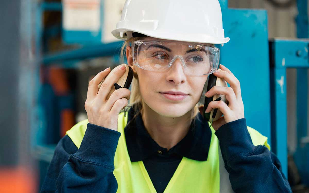 Woman construction worker putting on ear protection.