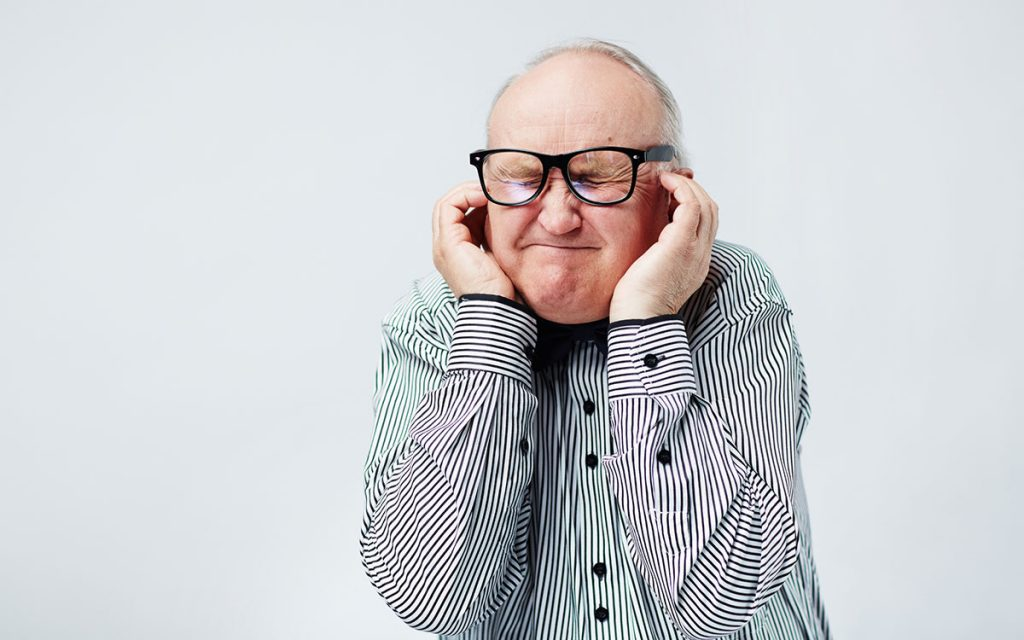 Man with his hand over his ears because of whistling hearing aids.