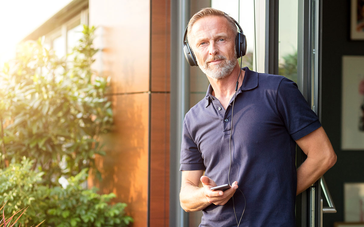 Middle aged man using headphones that might cause hearing loss.