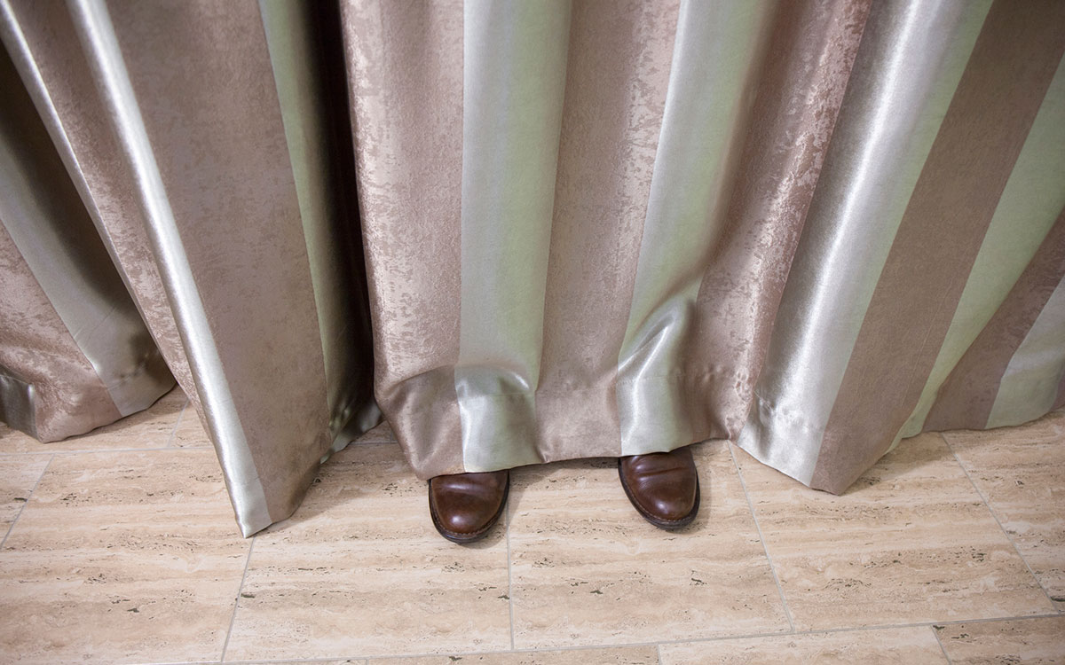 Shoes peeking out from under curtain symbolizing hearing loss as a hidden condition.