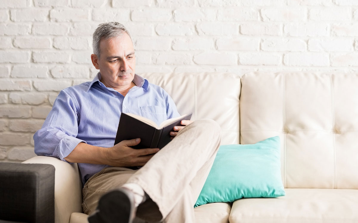 Alt image: Man learning how to use his hearing aids by reading aloud.