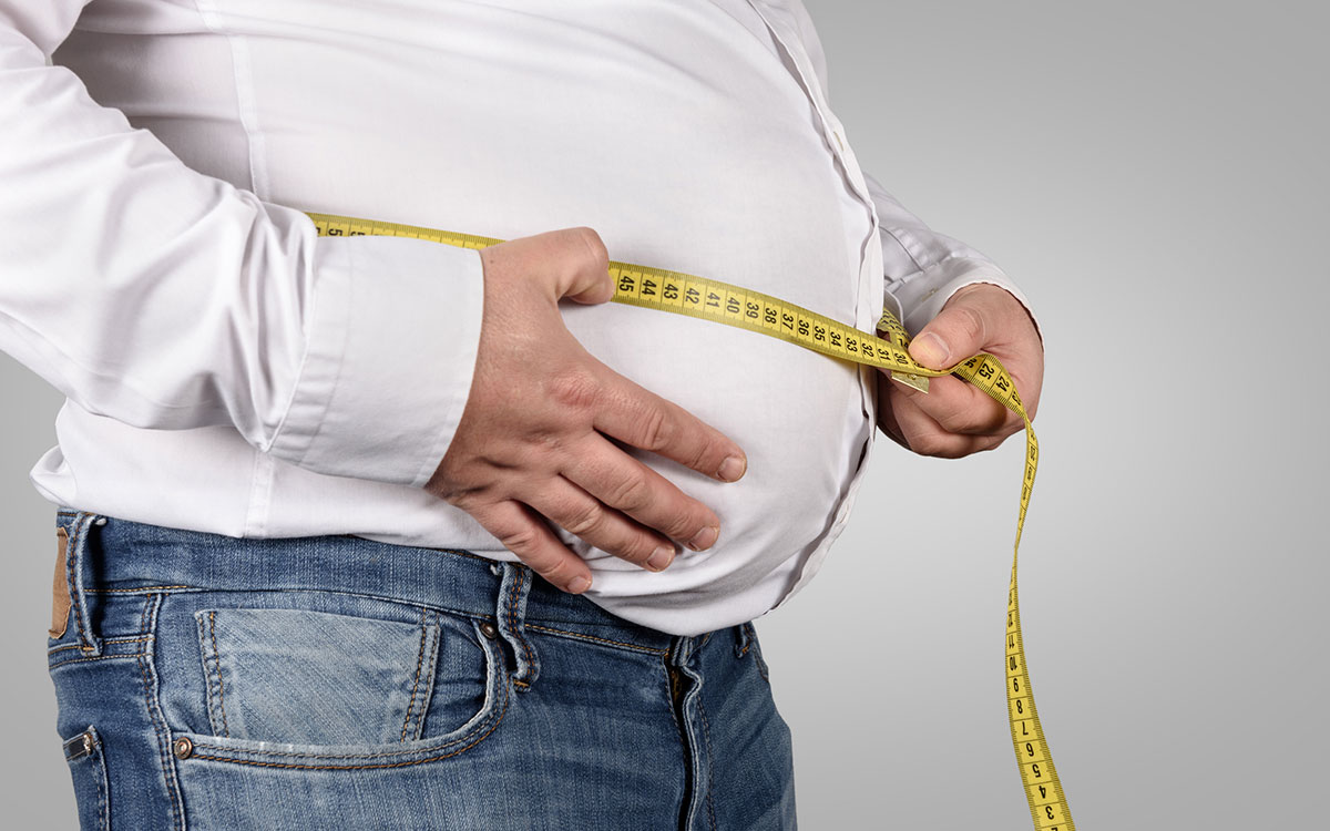 Man wirh measuring tape around his belly suffering from obesity and hearing loss.