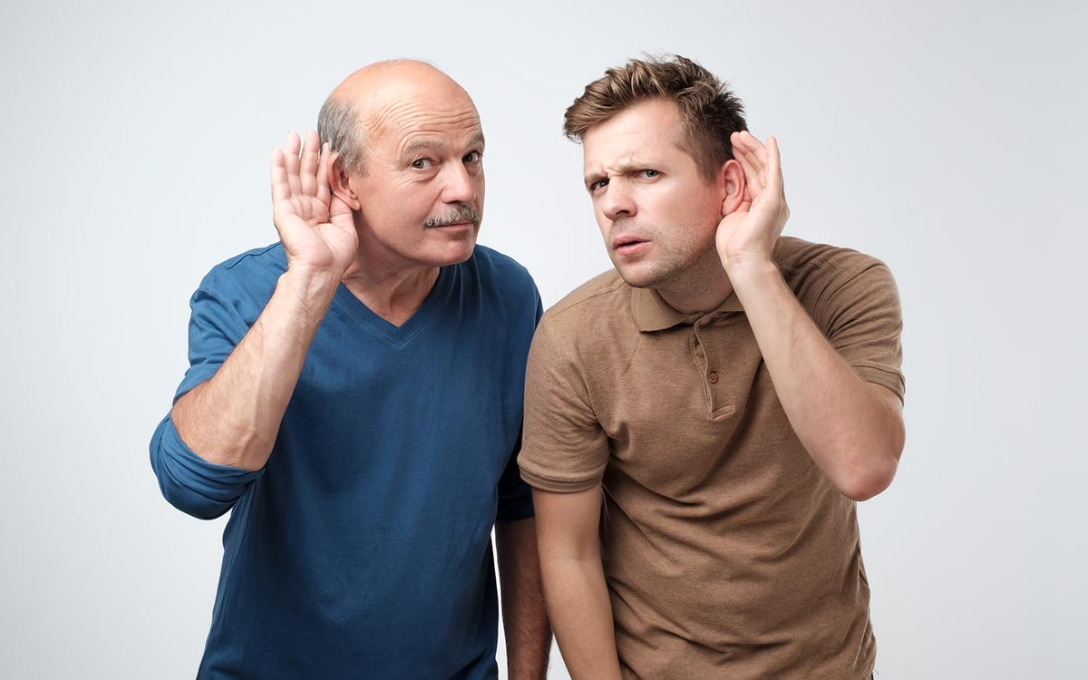 Two men with hands to their ears signifying hearing impairment.